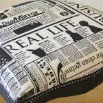 Zwarte eetkamerstoel met krantprint gestoffeerd